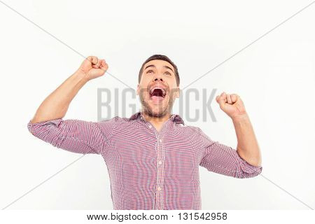 Attractive man screaming and showing fists  on a white background