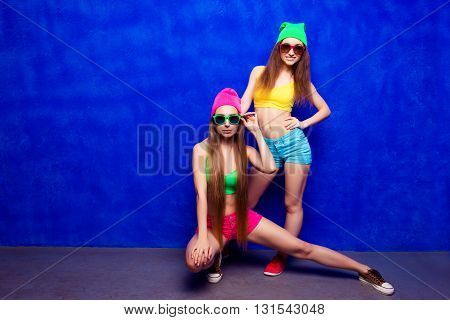 Stylish Young Woman Siting On Floor, Her Girlfriend Standing Near Her