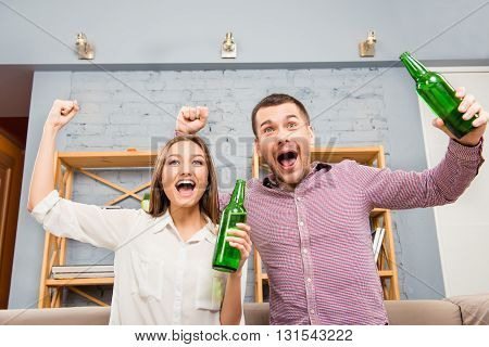 Happy Couple Watching Football With Beer And Triumphing With Raised Hands