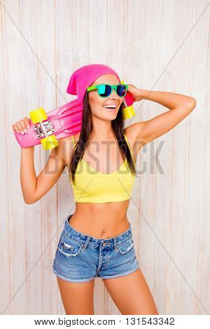 Cheerful Hipster Woman In Hat And Glasses Holding Skateboard