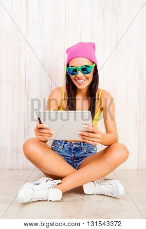 Smiling Woman In Hat And Spectacles Siting On Floor With Tablet