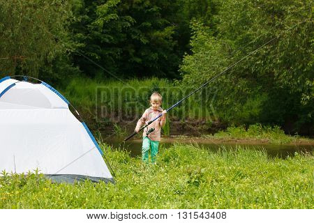 Cute Small Boy Fishing On The River. Camping On The Bank Of River
