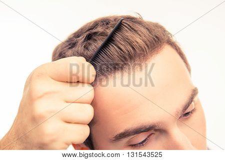 Closeup Photo Of Handsome Young Man Combing His Hair