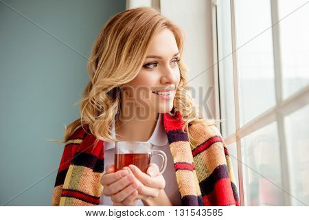 Smiling Woman Basking At Home With Plaid And Cup Of Hot Tea