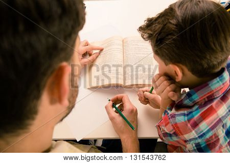 Close Up Portrait Of Father And Son Doing Home Task
