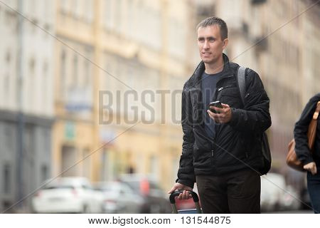 Portrait of young smiling handsome man with luggage bag walking on rainy city street holding cellphone using app gps searching for direction messaging travelling wearing casual clothes