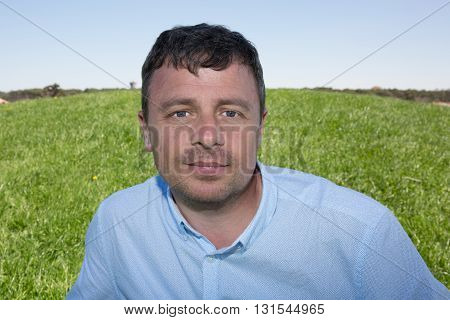 Man With Grass On The Background Looking At The Camera