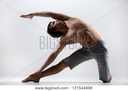 Sporty muscular young man working out yoga pilates fitness training doing side bend asana Parighasana Gate Yoga Pose gray background low key shot
