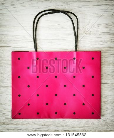 Beautiful red gift bag on the wooden background. Surprise theme. Paper bag. Vibrant colors. Shopping theme. Holiday symbol.