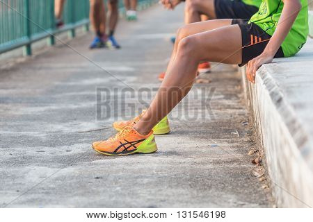 Close up runners legs with orange shoes