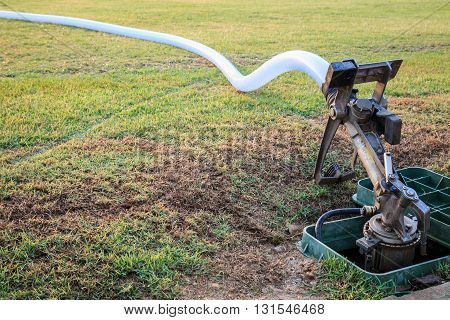 Sprinkler And Water Hose In Grass Field Football Stadium