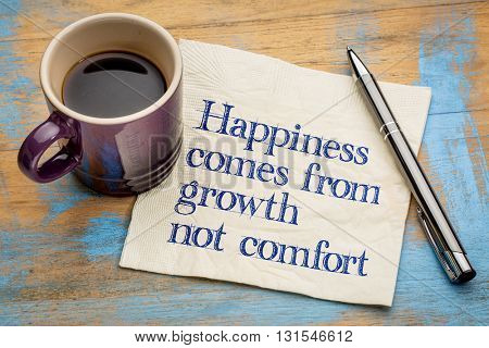 Happiness comes from growth, not comfort - inspirational handwriting on a napkin with a cup of espresso coffee