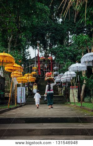 UBUD INDONESIA - MARCH 02: Balinese mother and son in traditional clothes going to the temple during Balinese New Year or Nyepi Day celebrations on March 02 2016 in Ubud Bali.