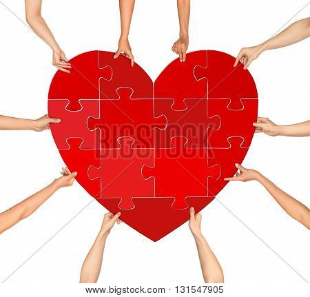 many hands holding puzzle heart isolated on a white background