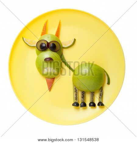 Funny goat made of green fruits on plate