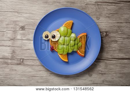 Fish made of green apple on plate and plank