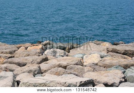 Background of a rocky sea shore with waves behind