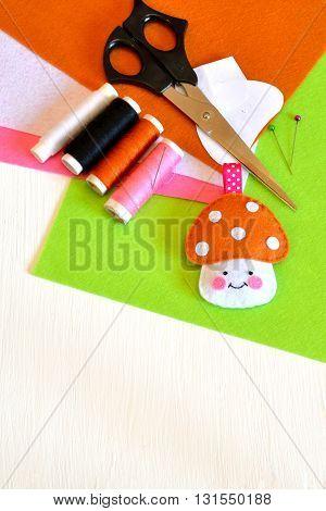 Felt mushroom, thread, needle, paper templates, pins, scissors. How to make handmade toy. Children's art background