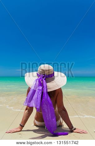 Woman in swimsuit relaxing at the beach on her holidays