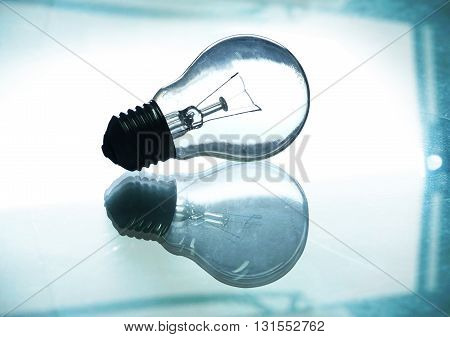 back light light bulb with reflection on the glass table