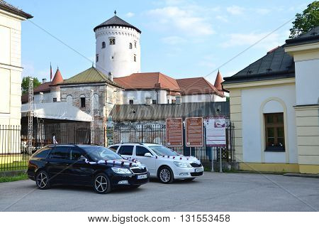 Zilina, Slovakia - May 20, 2016: Two cars dedicated for wedding guests decorated by white ribbon on car park in front of the Budatin castle.