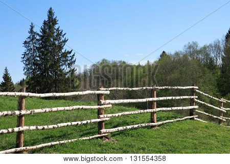 Fence made from wooden poles around field at summer