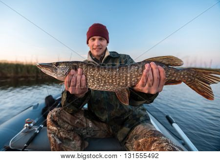 Happy young fisherman holding pike and sitting in the boat on the lake