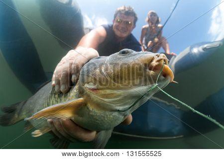 Underwater view of the man catching the fish