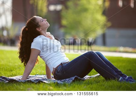 Happy young woman is sitting on the grass