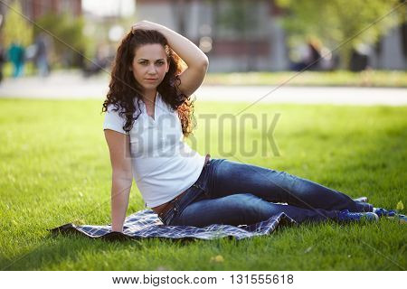 Beautiful young woman in jeans sits on the grass