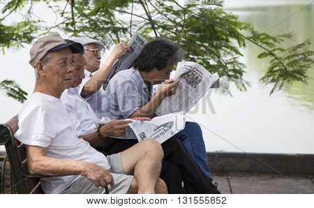 Hanoi, Vietnam - May 21, 2016: Vietnamese senior old men reading print newspaper at a park on the side of Hoan Kiem (Sword) lake, center of Hanoi capital and near the 36 old quarter street.