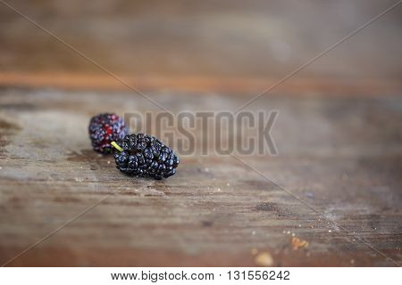 Mulberry berries on wooden table close up. Small DoF. Soft focus.