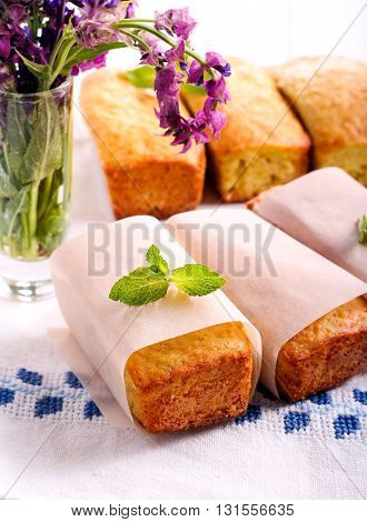 Mini loaf cakes with mint decoration on table