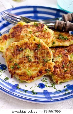 Courgette fritters with chopped dill on plate