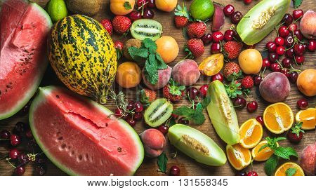 Various colorful tropical fruit selection on rustiv wooden background, top view. Watermelon, melon, strawberries, cherries, kiwi, peaches, apricots, oranges and limes. Horizontal