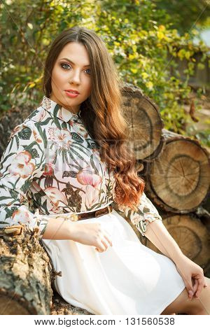 Portrait of beautiful brunette girl poses on nature background outdoors