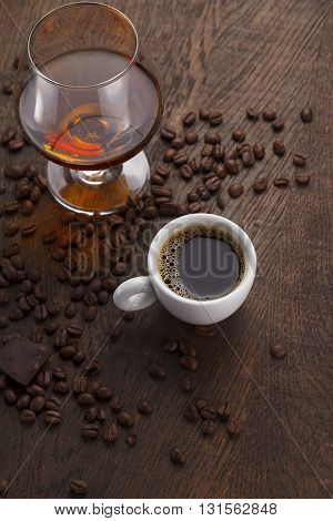 Cup Of Coffee, Cognac Glass And Coffee Beans On A Wooden Table