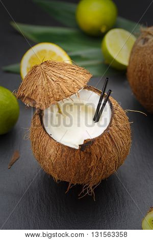 Coconut Cocktail On A Black Table With Lemon And Kiwi.