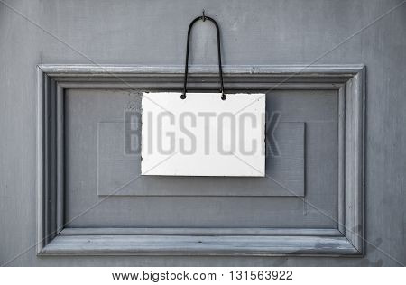 Empty white plate for information text hanging on gray wooden door