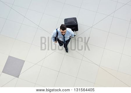 High angle view of businessman carrying his suicase