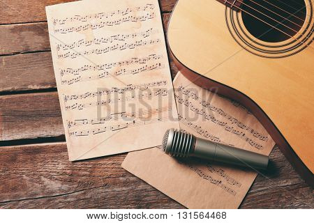 Guitar and microphone on wooden background