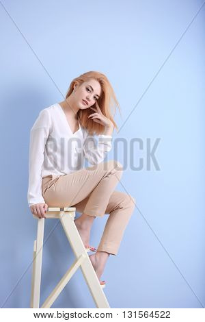 Beautiful blonde young woman in white shirt and beige pants on blue wall background