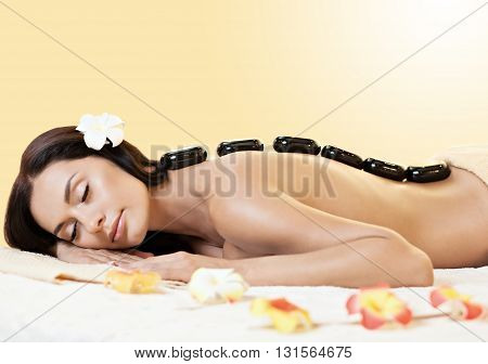 portrait of young beautiful woman in spa environment. Black stones on her back