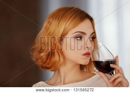 Young woman with glass of red wine on blurred background