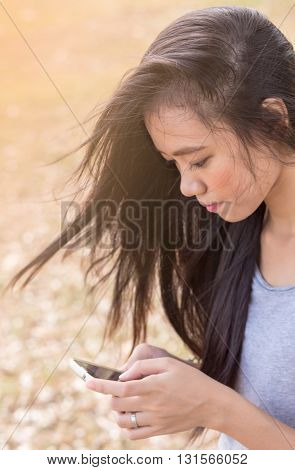 Woman Sitting In Garden Using A Mobile Telephone