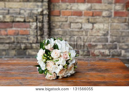 Round wedding bouquet of roses and freesias on the table