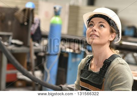 Factory worker using remote to lift goods
