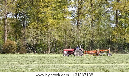LEUSDEN NETHERLANDS - MAY 6 2016: Farmer on the tractor pulling grass mower cutter through a lush green field.