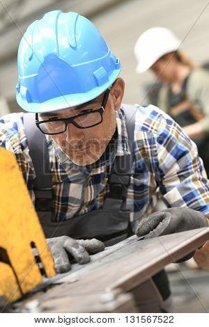 Metalworker in workshop using machine