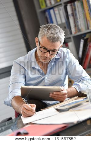 Businessman sitting in office working on tablet
